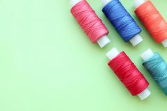 Multicolored bobbin of thread on a mint background stock photo