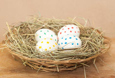 Four spotted colored easter eggs in hay Royalty Free Stock Images