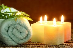 Four square candles and blue towel. Four square candles, blue towel and green leaf ready for spa bath Stock Photo