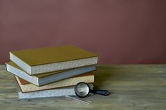 Four stamp albums books bunch, magnifier and tweezers on wooden table and bordeaux background royalty free stock photo