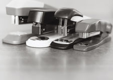 Four staplers on wooden background. Black and white photo Royalty Free Stock Image