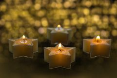 Four star shaped candles are burning in the dark stock image
