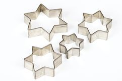 Four star shaped Christmas cookie cutters over white Royalty Free Stock Images