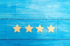 Four stars on a blue background. The concept of rating and evaluation. The rating of the hotel, restaurant, mobile application. Qu. Ality service, buyer choice stock image