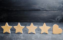 Four stars and heart on a black background. rating five stars, the choice of the editorial office and the buyer. concept of rating royalty free stock photography
