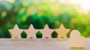 Four stars and heart on a green bokeh background. rating five stars, the choice of the editorial office and the buyer. concept of stock photography