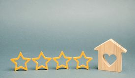 Four stars and a wooden house on a gray background. Success. Feedback. Good evaluation of the critic. Hotel rating. Quality of stock photo