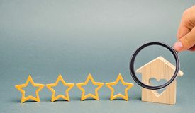 Four stars and a wooden house on a gray background. Success. Feedback. Good evaluation of the critic. Hotel rating. Quality of royalty free stock photo