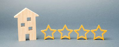 Four stars and a wooden house on a gray background. Success. Feedback. Good evaluation of the critic. Hotel rating. Quality of stock image