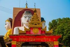 Four statues of sitting Buddhas. Pagoda Kyaikpun Buddha. Bago, Myanmar. Burma. Stock Photography
