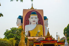 Four statues of sitting Buddhas. Pagoda Kyaikpun Buddha. Bago, Myanmar. Burma. Stock Image