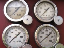 Four steel-rimmed pressure gauges on maroon-red background stock photo