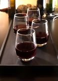 Red wine in four stemless glasses. Four stemless glasses of red wine on a black tray with bottles and bread in the background royalty free stock photos