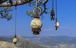 Four stone idol hanging on a pine tree in the Crimean mountains Royalty Free Stock Images