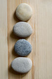 Four stones are aligned in a line on light wood background Stock Images
