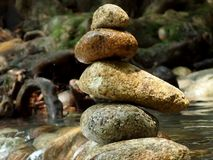 Four stones balanced. Balanced stones or stone pyramid on the river bank royalty free stock photos