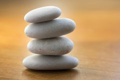 Stone cairn tower, poise stones, rock zen sculpture, light white pebbles on wooden background. Four stones cairn tower, poise stones, rock zen sculpture, light royalty free stock image