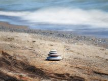 Four stones stacked on rustic driftwood on beach, waves crashing. Behind. Calm color image stock photo