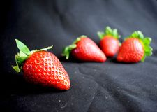 Four strawberries on black fabric stock photo