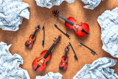 Four string musical orchestra instruments: violin, cello, contrabass, viola and crumpled sheet music lying near them on a wooden b Stock Photo