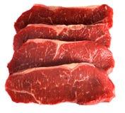 Four striploin steaks on white