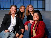 Four students being friendly and serious. Four young student friends posing on stairs Royalty Free Stock Image