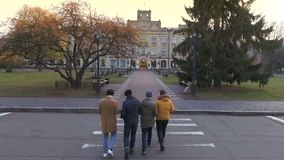 Four students goes to university, aerial view. Four students goes to the university on lectures. Young guys goes to the entrance door of campus through a road stock video