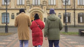 Four students goes to university. Four students stands near the university and discussing some educational material from lectures. Four young people talks with stock footage