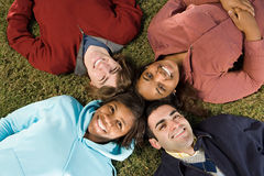 Four students lying down outdoors Royalty Free Stock Images