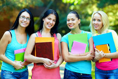 Four students  posing outside in green park Stock Image