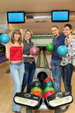 Four students stand near tenpin bowling with balls. For playing bowling and smile, focus on girl in center Royalty Free Stock Photo