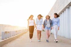 Four students walking down walkway stock photo