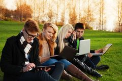 Four students working on laptops in the park. Four students, two couples working on laptops in the spring evening park royalty free stock image