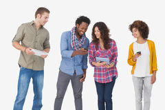 Four stylish friends looking at tablet and holding phones. On white background Royalty Free Stock Images