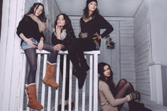 Four stylish models posing sitting on the fence Royalty Free Stock Photo