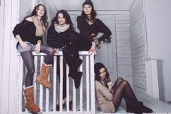 Four stylish models posing sitting on the fence Stock Photos