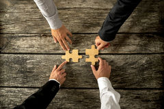 Four successful business men joining two puzzle pieces each bein. G held by two partners, rustic wooden background. Conceptual of merger or creative cooperation Royalty Free Stock Photos