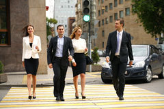 Four successful business people crossing the street in the city Stock Photo