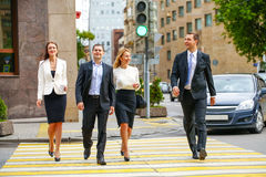 Four successful business people crossing the street in the city Stock Image
