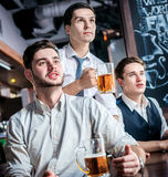 Four successful business people drinking beer and rejoice and sh Royalty Free Stock Images