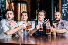 Four successful business people drinking beer and rejoice and sh Stock Photos
