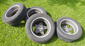 Four summer tires with alloy wheels. Lying in a meadow Royalty Free Stock Photo