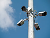 Four surveillance cameras horizontally. Four surveillance cameras positioned on the pole lanterns schoolyard Royalty Free Stock Image