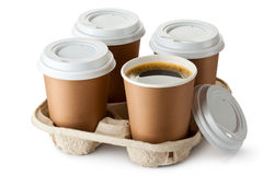 Four take-out coffee in holder. One cup is opened. Standing on a white Royalty Free Stock Photos