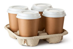 Four take-out coffee in holder. Standing on a white Royalty Free Stock Image