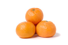 Four tangerines on a white. Four tangerines in the form of a pyramid on white Royalty Free Stock Images