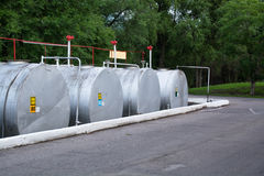Four tanks for flammable liquids located horizontally. Cisterns located on the paved area and surrounded by a border Stock Image