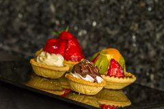 Four tarts on black reflective bench top angled stock photos