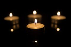Four Tea Candles with Reflection on Black Royalty Free Stock Image