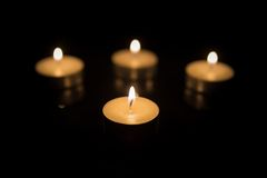 Four Tea Candles with Reflection on Black Royalty Free Stock Photos